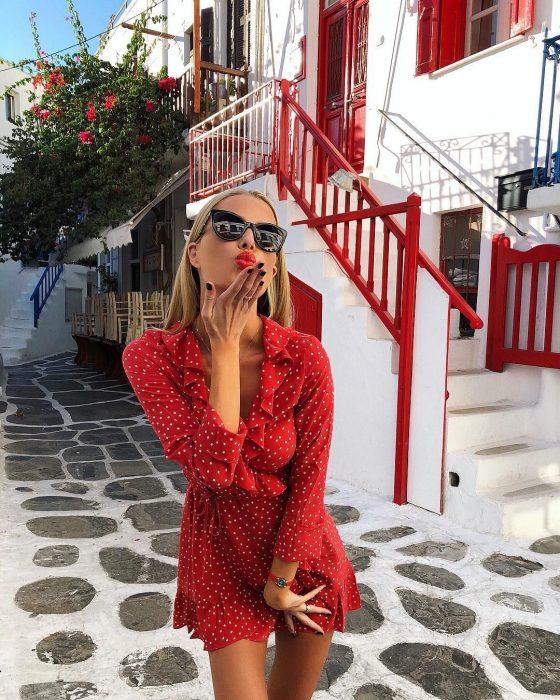 mujer con vestido rojo enviando beso