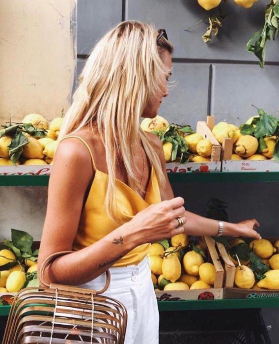 chica comprando limones