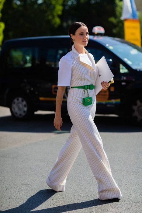 Chica usando una mini bolsa de color verde con un traje blanco
