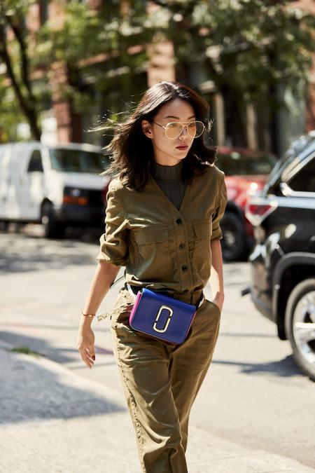 Chica caminando mientras usa un mono verde y una bolsa morada