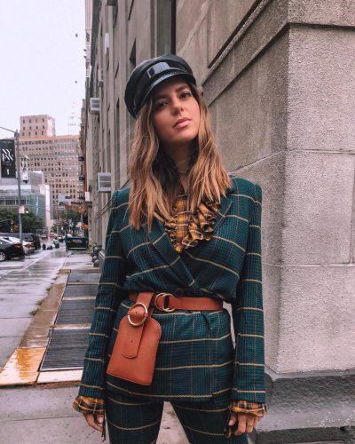 Chica usando una bolsa como cinturón sobre un traje de color verde