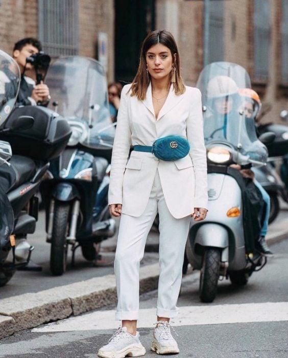 Chica usando un traje blanco con una bolsa riñonera color azul