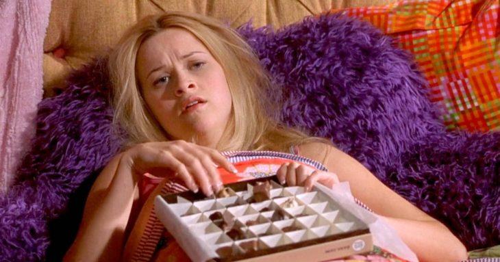 Chica comiendo chocolates en la cama