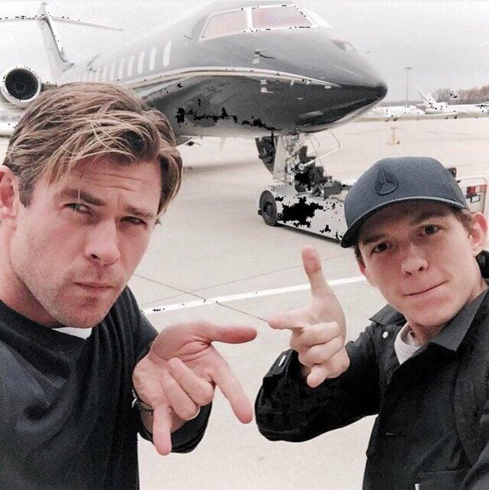 hombres junto a avión haciendo seña de hombre araña