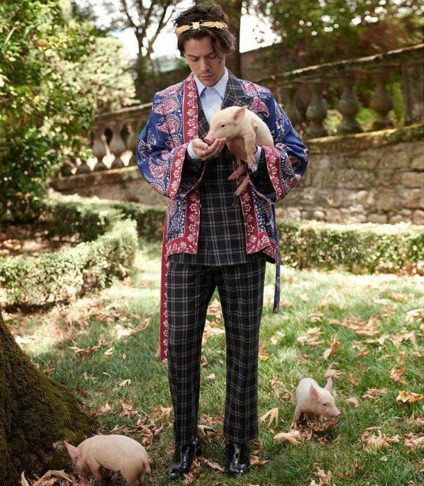 Harry Styles cargando un cochino para la campaña de gucci