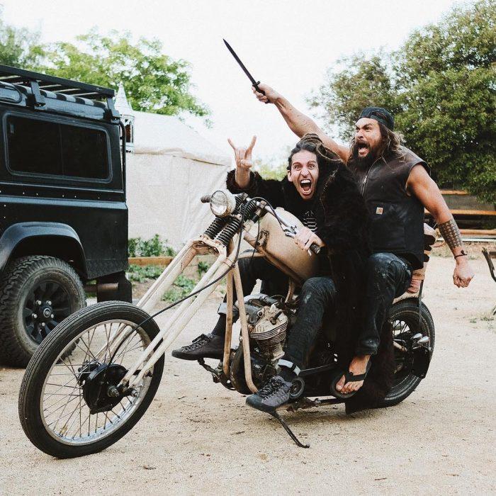 Jason Momoa sobre una motocicleta conducida por uno de sus amigos