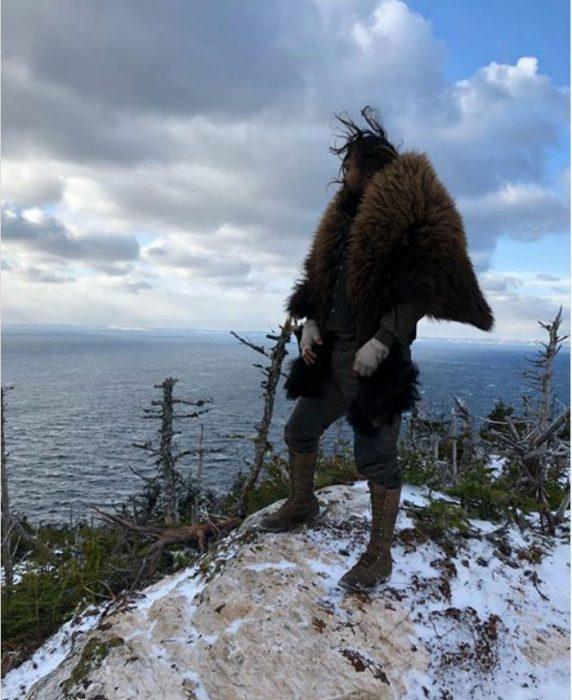 Jason Momoa parado sobre una roca cubierto con un sueter de pieles