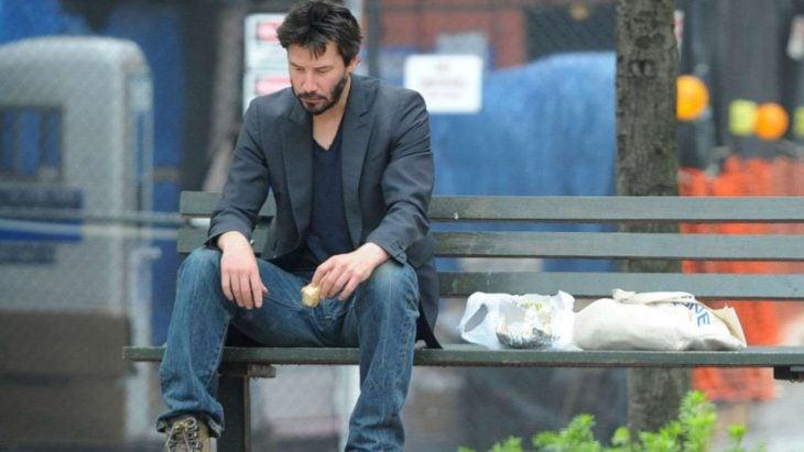 Keanu Reeves sentado en una banca comiendo helado