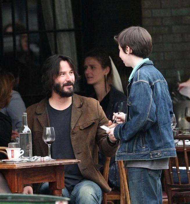 Keanu Reeves conversando con un niño mientras come