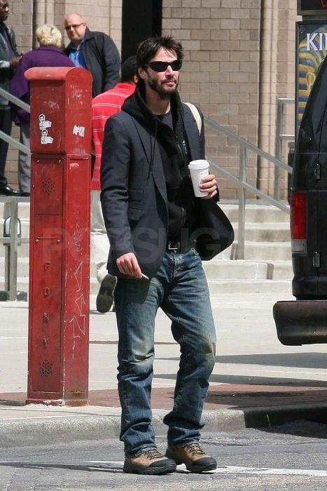Keanu Reeves tomando café mientras camina por la calle
