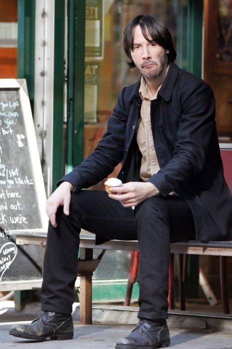 Keanu Reeves sentado en una banca comiendo un helado