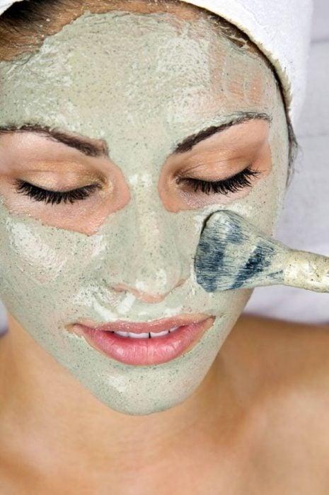 Chica aplicandose una mascarilla natural en el rostro