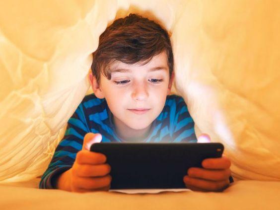 Niño sosteniendo una tablet mientras está bajo las cobijas