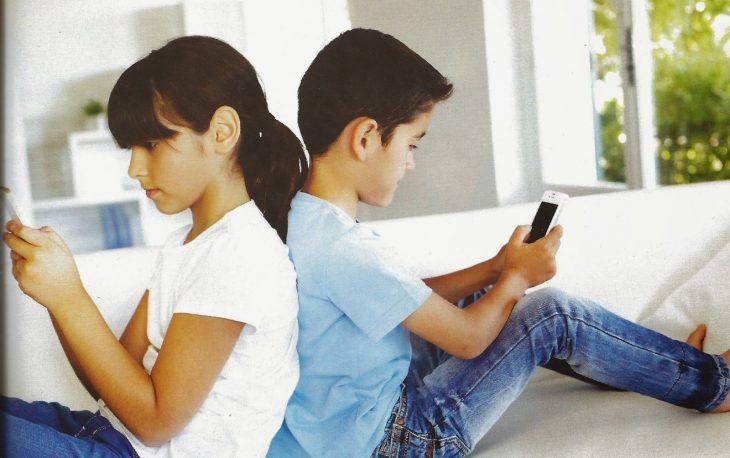 Niños sentados de espaldas revisando cada uno su celular