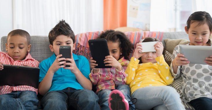 Niños sentados en unsofá sosteniendo cada uno su celular