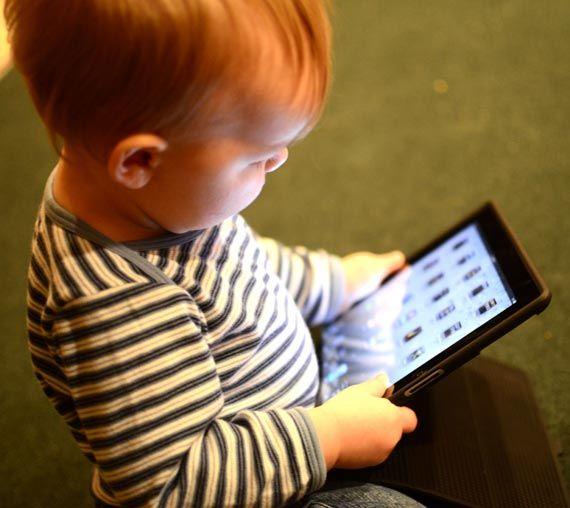 Niña de dos años sosteniendo una tabler
