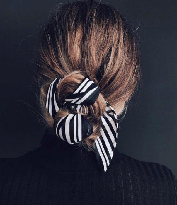 Chica usando una mascada en el cabello para sujetar su pelo
