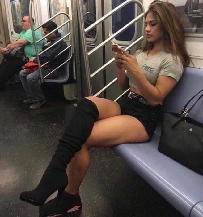 Mujer sentada en el metro usando una zapatilla y una bota