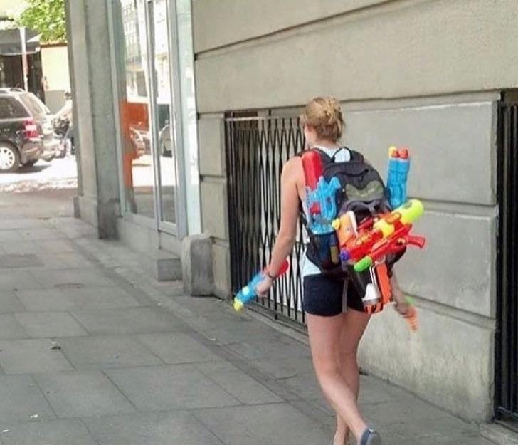 Mujer caminando por la calle mientras sostiene pistolas de agua