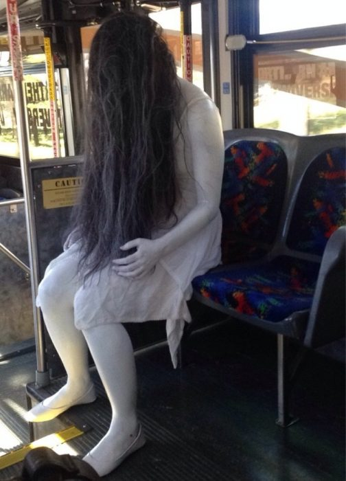 Mujer vestida como la chica del aro en el autobus