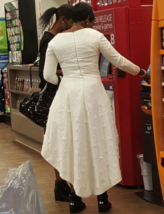 Mujer usando su vestido de novia mientras está en el supermercado