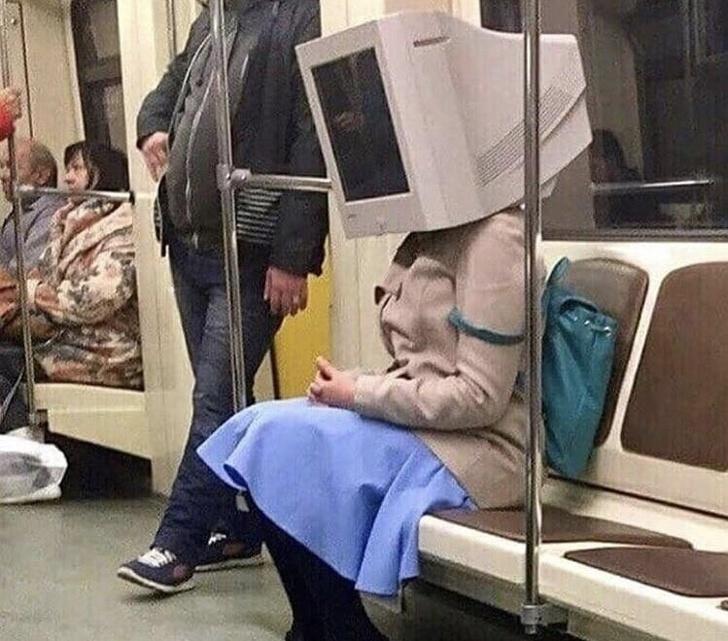 Mujer usando una computadora como sombrero