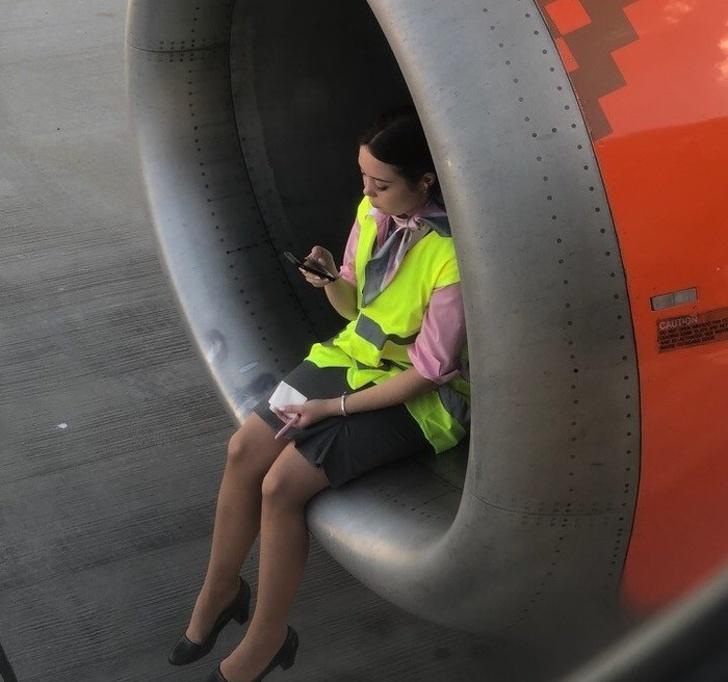 Mujer sentada en una turbina de avión mientras revisa su celular