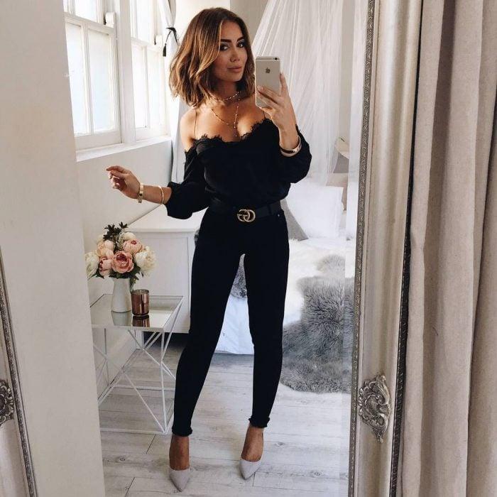 Chica usando un pantalón y top de color negro con cinto de gucci