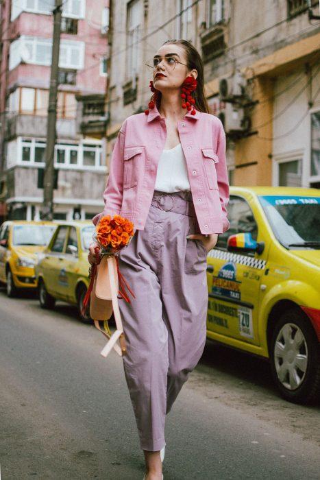 mujer con chaqueta rosa pastel y aretes rojos