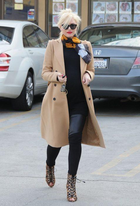 mujer con saco caqui y pantalones de mezclilla