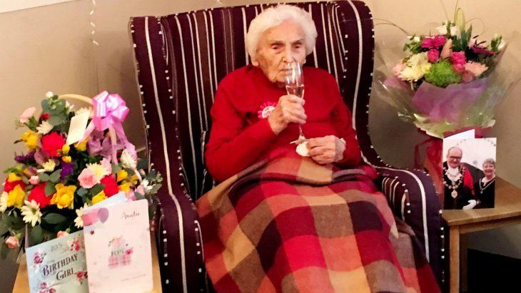 mujer anciana sentada en sillon vestida de rojo