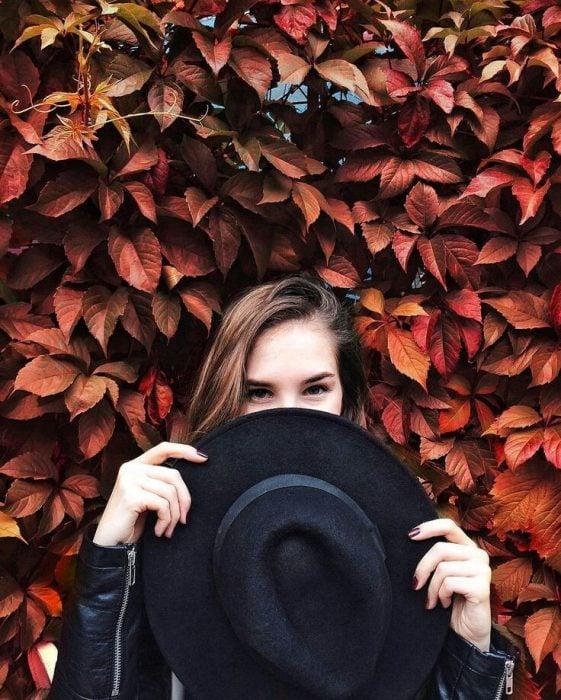 Mujer con pared de hojas naranjas y sombrero