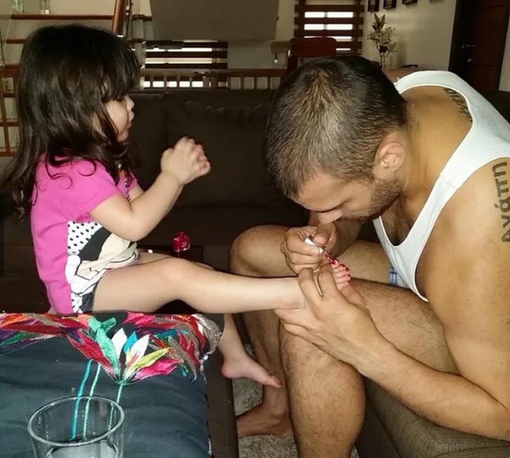 hombre pintando las uñas de su hija