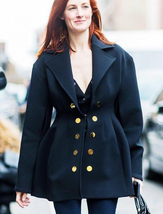 mujer pelirroja con ropa negra y abrigo