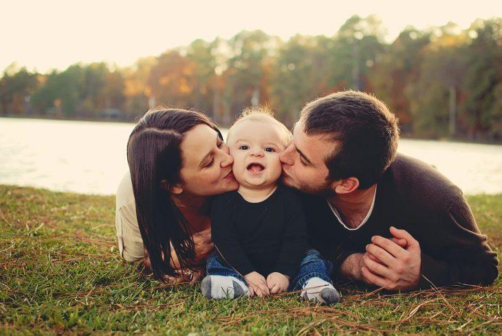 Familia posando para foto en el pasto; mamá y papá dando beso en el cachete a su bebé sonriente
