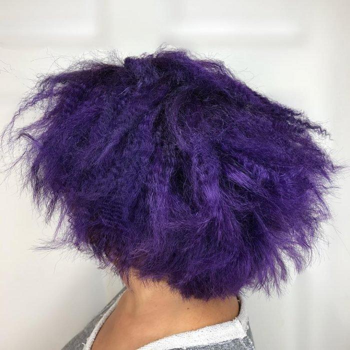 Mujer con cabello morado muy maltratado