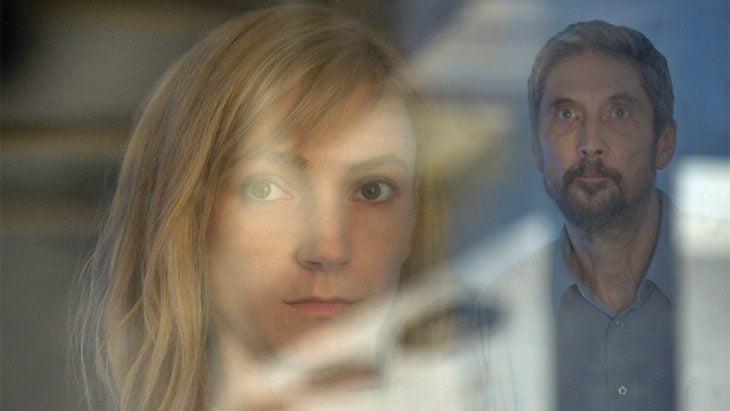 mujer rubia y hombre doctor detrás de vidrio