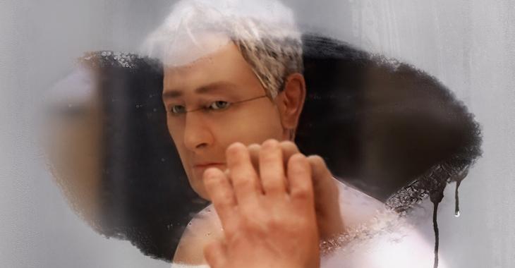 hombre con lentes y canas con manos en el espejo