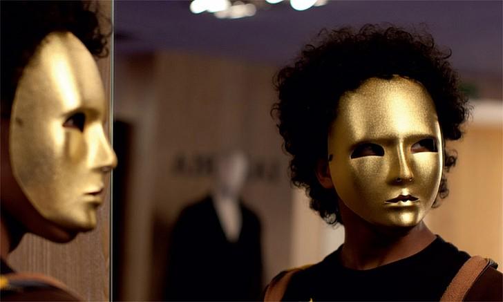 hombre con cabello rizado y mascaras doradas