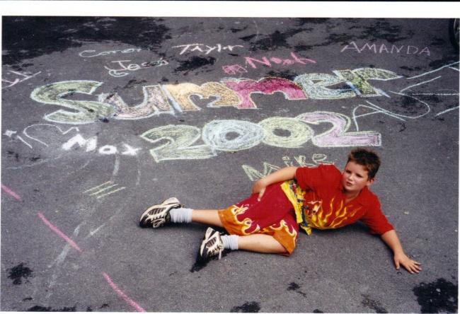 niño tirado en el suelo con pintura de gis