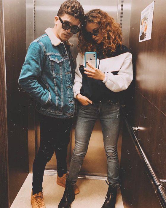 mujer de cabello chino con chamarra y celular junto a hombre selfie elevador