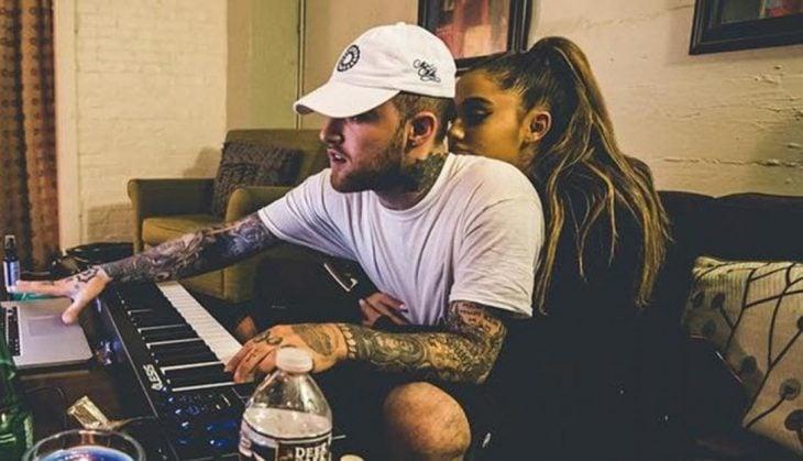 hombre con gorra blanca tocando el piano y mujer atrás abrazandolo
