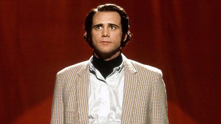 Jim Carrey parado frente a una cortina roja