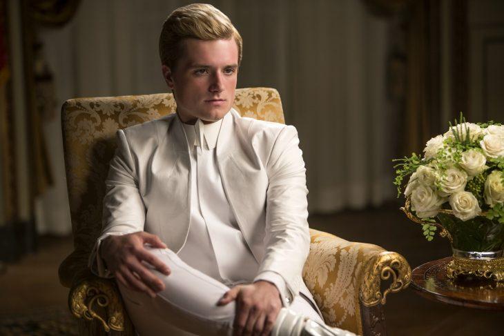 Chico de traje blanco sentado en un sillón elegante