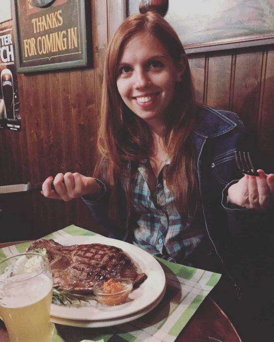 Chica comiendo carne roja