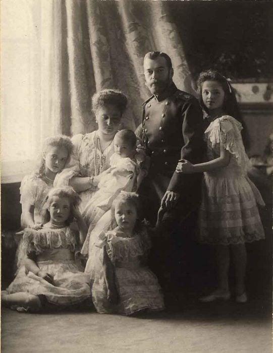 Retrato real de la familia Romanov posando junto a una ventana