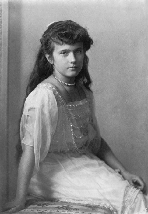 Retrato real de Anastasia posando sentada con un vestido y su collar de perlas