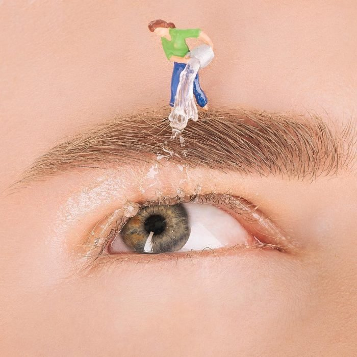 Chica con una ceja pintada mientras le echan agua a un ojo