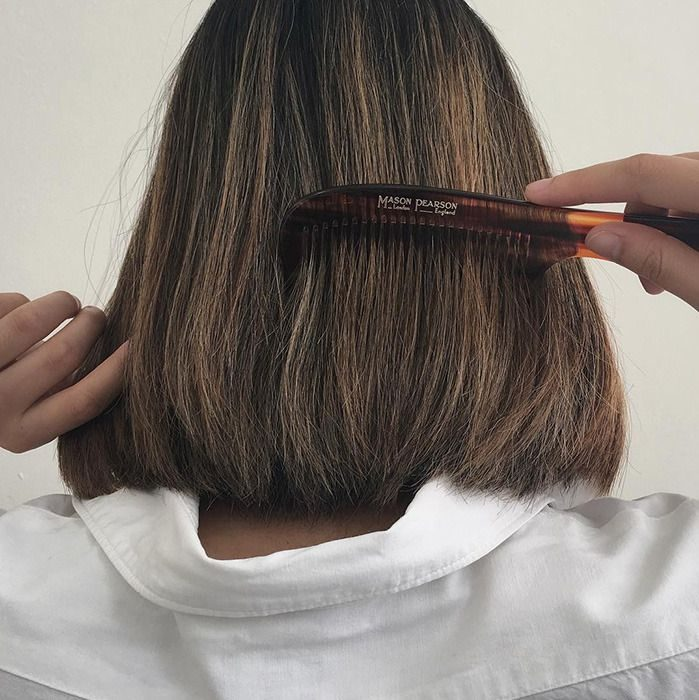 Chica peinándose el cabello con corte de hongo