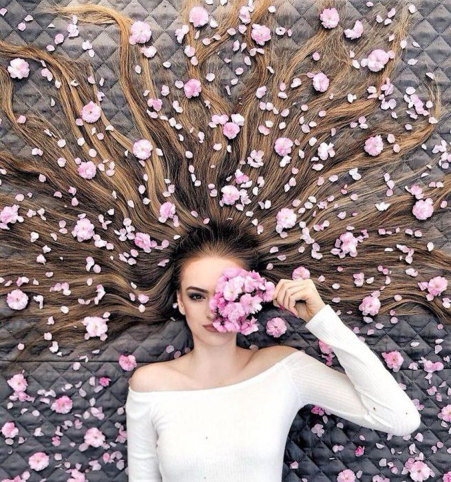 chica cubriendo su ojos con una rosa y modelando